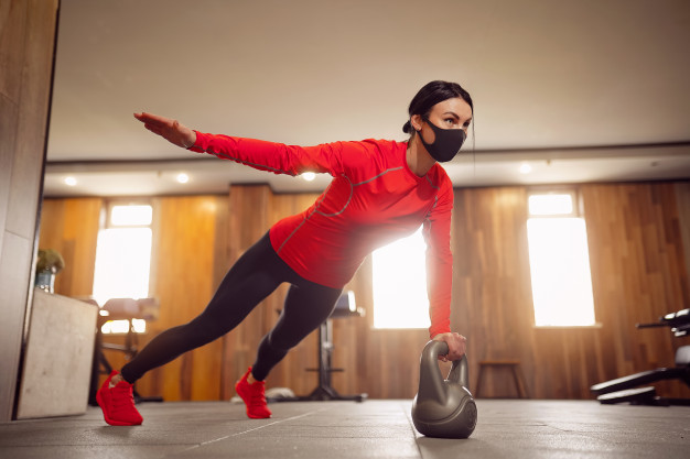 sport-girl-mask-from-coronavirus-doing-kettlebells-planking_136403-7555